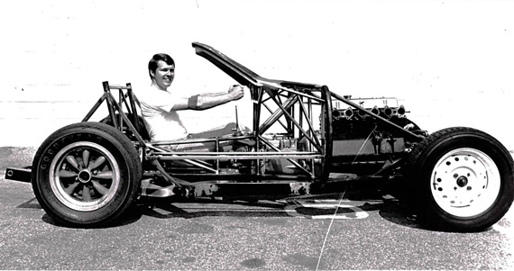 "Peter Brock sits in his partially completed TR250K chassis. Note the 9"" engine set back and that the specially fabricated intake manifold has now been fitted."