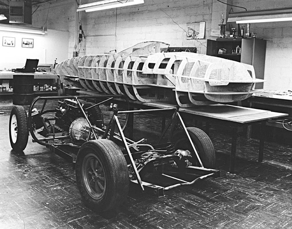 The bare TR4 chassis (note the independent rear suspension) in the BRE shop with the finished TR250K wooden buck on the fabrication table just behind. Brock's stiffening tubular sub-frame has not yet been added.