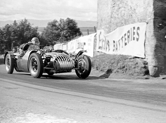 Peter Hughes photographed in action with the car at Bo'ness hill Climb in 1953. Struggling with it as you can see by the arm action.  (Photo Graham Gauld.)